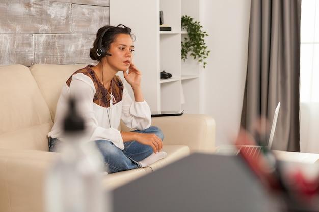 Femme portant des écouteurs lors d'un appel vidéo de travail tout en travaillant à domicile.