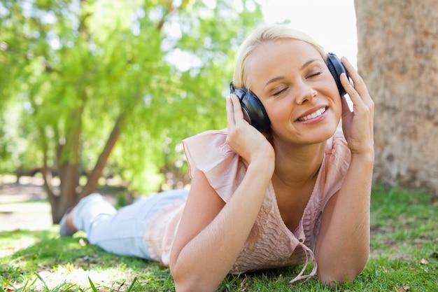 Femme portant des écouteurs en position couchée sur la pelouse