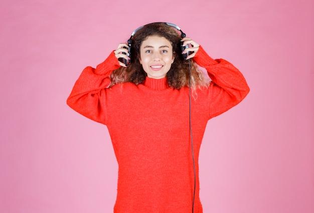 Femme portant des écouteurs pour écouter de la musique.