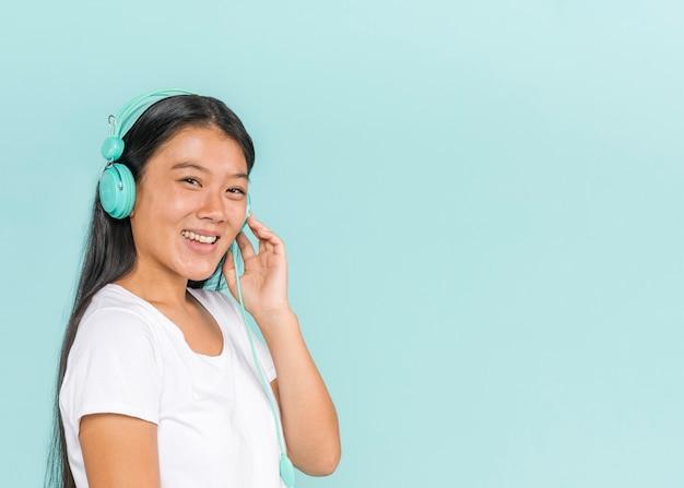Femme portant des écouteurs et souriant