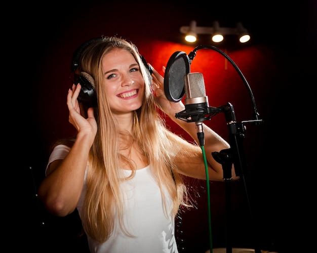 Femme portant des écouteurs et sourit