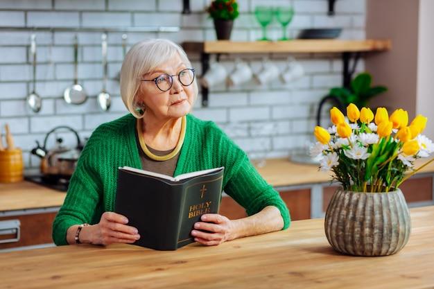 Femme portant un élégant cardigan vert et des lunettes tenant un livre de la sainte bible ouvert