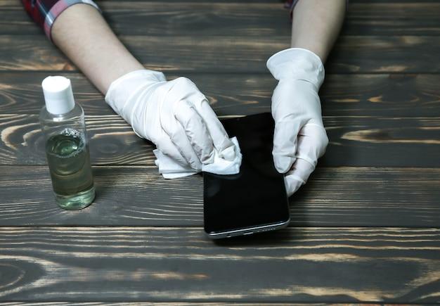 Une femme portant des gants en caoutchouc désinfecte son smartphone avec des cotons. antiseptique pendant la pandémie de coronavirus. danger de virus. gadgets dangereux sales. mesures de sécurité.