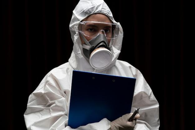 Femme portant des gants avec une combinaison de protection chimique contre les risques biologiques et un masque. écrit sur du papier.