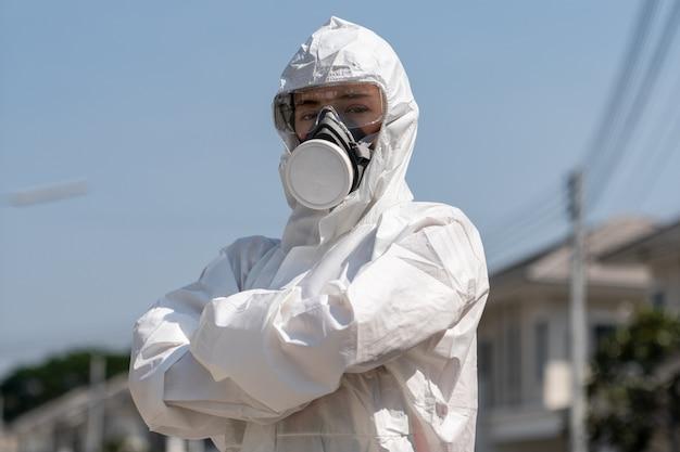 Femme portant des gants avec une combinaison de protection chimique contre les risques biologiques et un masque. elle croisa les bras avec un visage malheureux.
