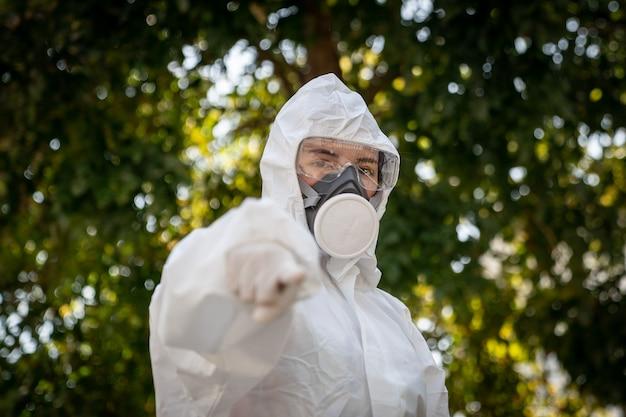 Femme portant des gants avec une combinaison de protection chimique contre les risques biologiques et un masque. pointant le doigt vers vous