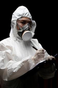Femme portant des gants avec une combinaison de protection chimique contre les risques biologiques et un masque. rédige un rapport sur papier.