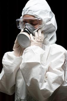 Femme portant des gants avec une combinaison de protection chimique contre les risques biologiques et un masque.