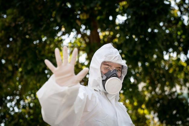 Femme portant des gants avec une combinaison de protection chimique et un masque contre les risques biologiques. avec un visage malheureux. femme tient la main devant elle, signe pour arrêter, panneau d'arrêt.