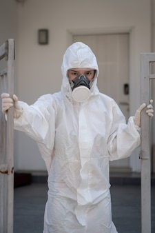 Femme portant des gants avec une combinaison de protection chimique et un masque contre les risques biologiques. avec un visage malheureux. ouverture d'une porte en fer.