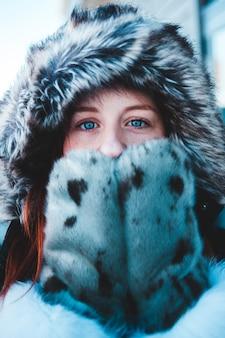 Femme portant des gants et un manteau de fourrure blanc et noir