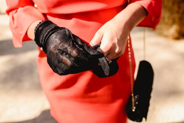 Femme portant des gants noirs et une élégante robe de soirée rouge.