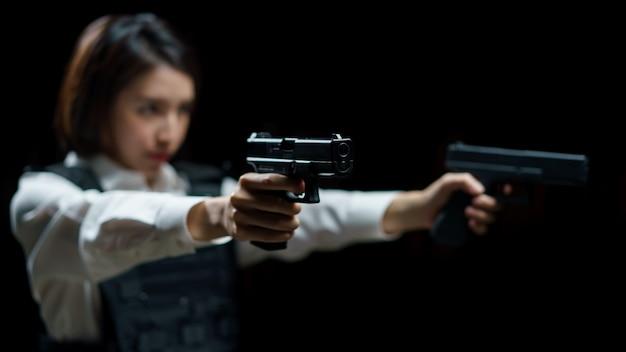 Femme portant un gilet pare-balles tire avec un pistolet sur une cible au champ de tir intérieur.