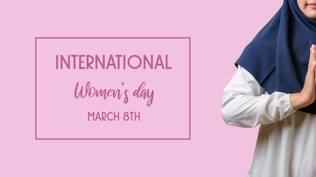 Une femme portant le hijab avec une main de bienvenue sur fond rose et inscription journée internationale de la femme