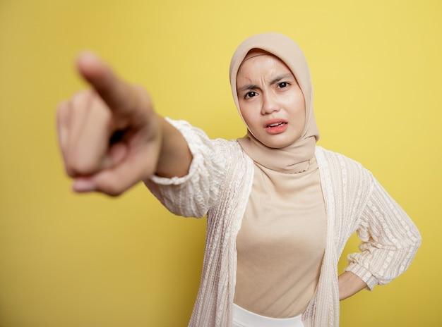 Femme portant le hijab pointe vers une personne isolée sur un mur jaune