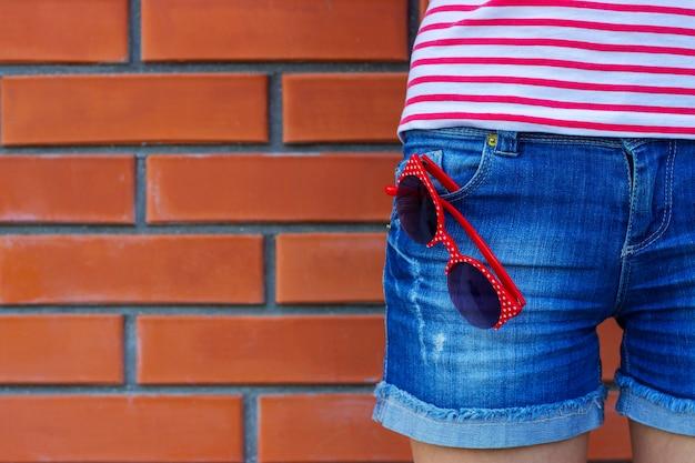 Femme portant des jeans avec une paire de lunettes de soleil dans la poche.
