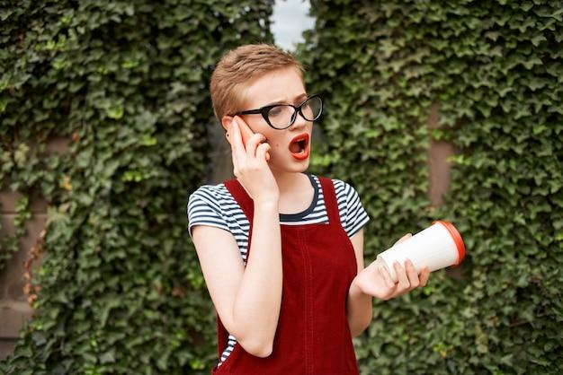 Femme portant des lunettes aux cheveux courts tasse de café à l'extérieur