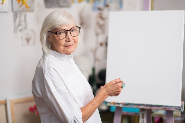 Femme portant des lunettes. belle femme aux cheveux blonds à la retraite portant des lunettes avant de peindre en atelier