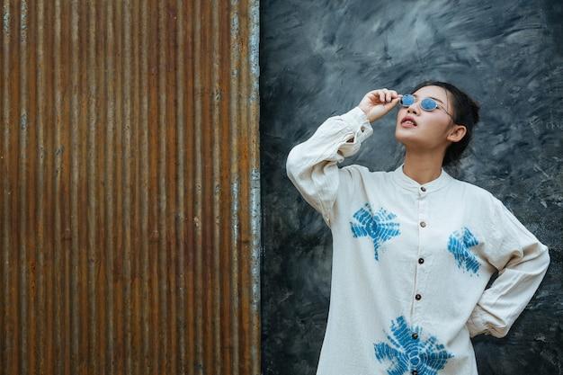 Une femme portant des lunettes indique que le ciment est gris et rouille.
