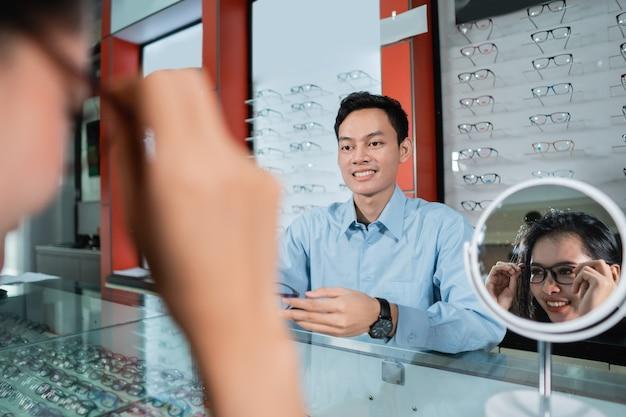 Une femme portant des lunettes et se reflétant dans un verre dans le contexte d'une vitrine de lunettes et d'un employé dans une clinique ophtalmologique