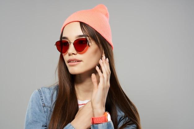 Femme portant des lunettes de soleil chapeau rose fashion style moderne posant sur fond gris