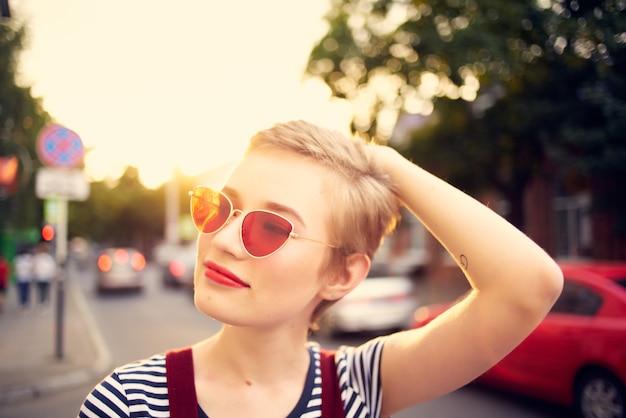 Femme portant des lunettes de soleil à l'extérieur marche émotions mode posant