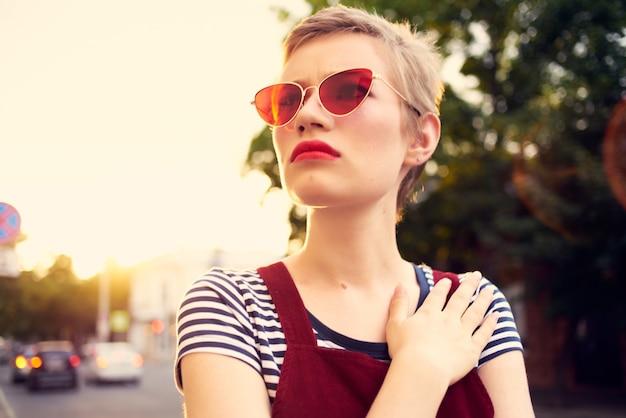 Femme portant des lunettes de soleil à l'extérieur posant la mode estivale