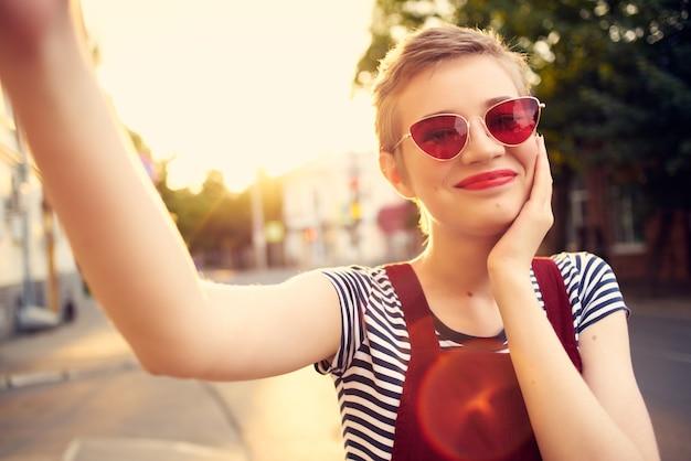 Femme portant des lunettes de soleil à l'extérieur posant une romance de mode amusante. photo de haute qualité