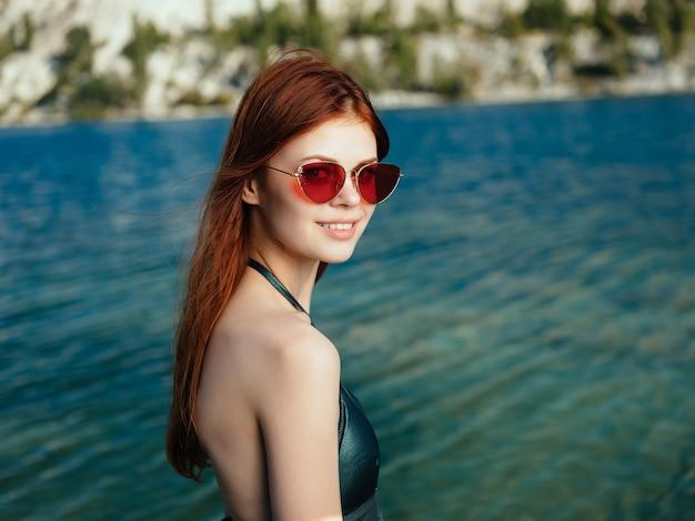 Femme portant des lunettes de soleil à l'extérieur rivière posant reste maillot de bain vert. photo de haute qualité
