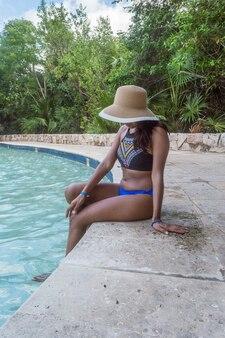 Femme portant un maillot de bain avec un chapeau brun assis sur le bord de la piscine tout en regardant l'eau