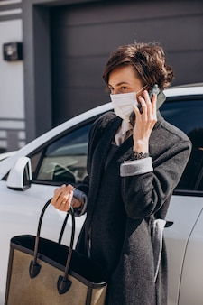 Femme portant un masque facial debout près de sa voiture