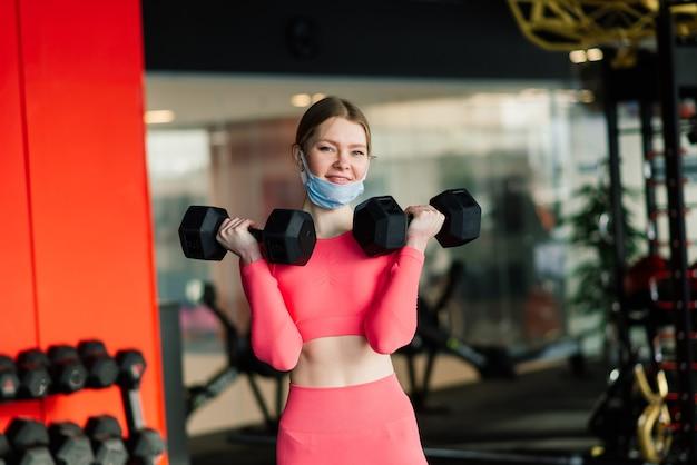 Femme portant un masque facial exercice d'entraînement dans la salle de gym pendant la pandémie du virus corona.
