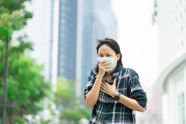 Une femme portant un masque facial protège le filtre contre la pollution de l'air (pm2,5) ou porte du n95