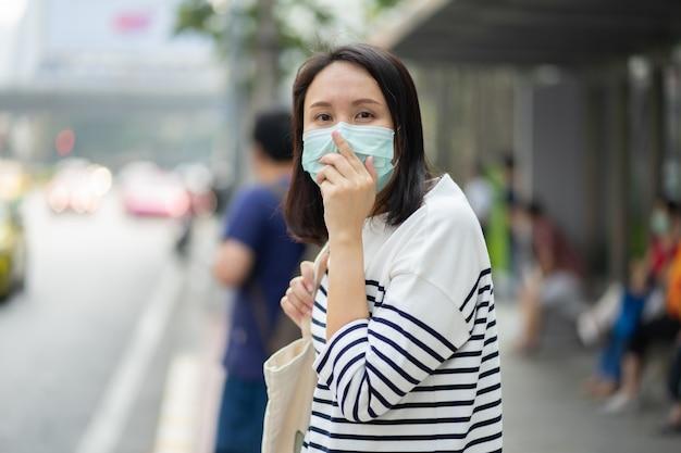 Une femme portant un masque facial protège le filtre contre la pollution de l'air (pm2,5) ou porte du n95