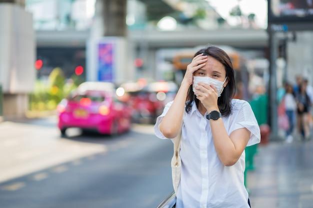 Une femme portant un masque facial protège le filtre contre la pollution de l'air (pm2.5)