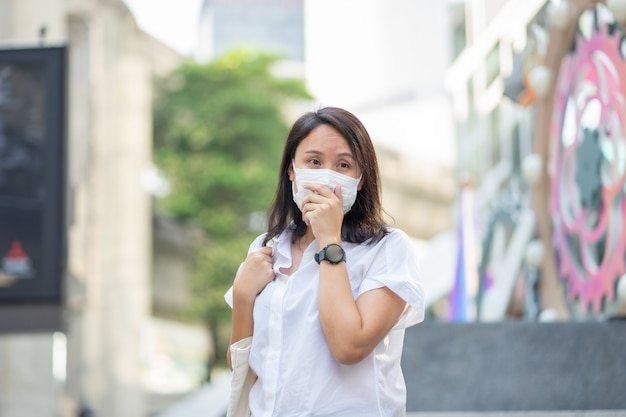Une femme portant un masque facial protège le filtre contre la pollution de l'air (pm2.5)