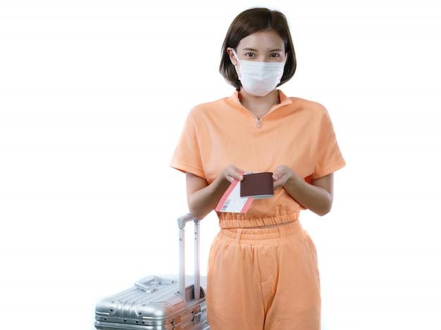 Femme portant un masque facial, tenant un passeport de bagages et une carte d'embarquement