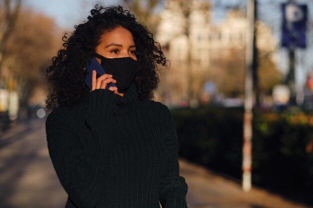 Femme portant un masque facial tout en parlant au téléphone.