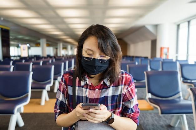 Une femme portant un masque facial voyage sur l'aéroport, un nouveau voyage de style de vie après le covid-19.
