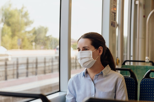 Femme portant un masque facial voyageant en tramway. elle regarde par la fenêtre. nouveau concept normal