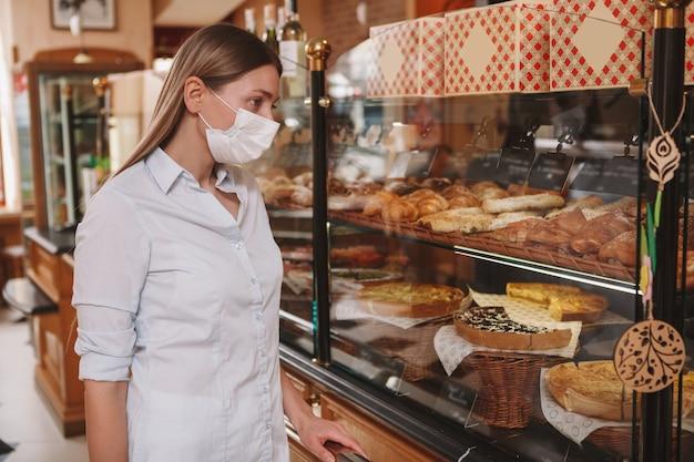 Femme portant un masque médical, acheter des pâtisseries pendant la quarantaine du coronavirus, espace copie