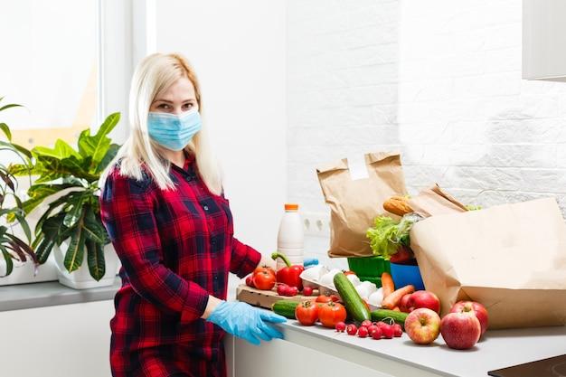 Femme portant un masque médical démonte les sacs de nourriture à la maison dans la cuisine. quarantaine. notion de santé. corona virus. commande de produits en ligne. livraison de produits à domicile