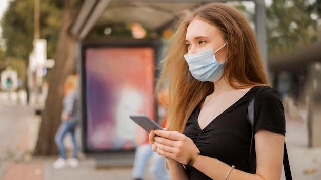 Femme portant un masque médical à l'extérieur
