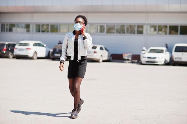 Femme portant un masque médical jetable et des gants marcher en plein air et parler au téléphone pendant la période épidémique.