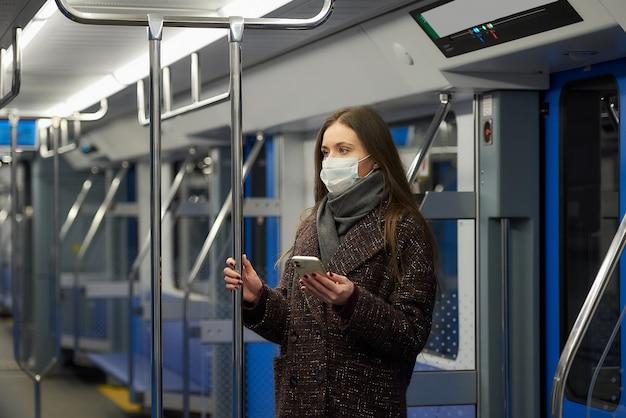 Une femme portant un masque médical pour éviter la propagation du coronavirus est debout et tient un téléphone dans une voiture de métro moderne