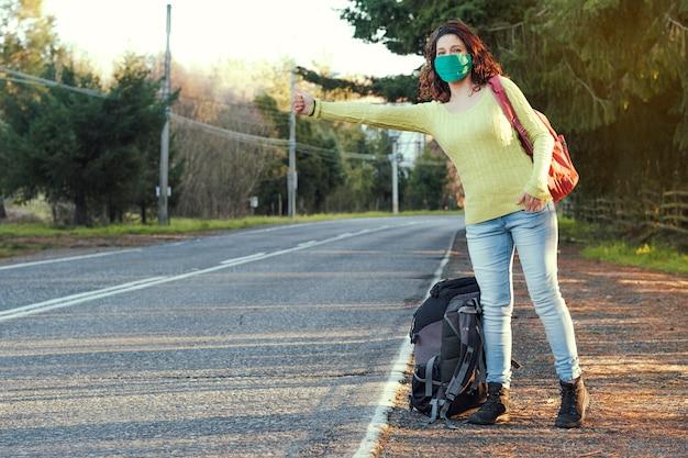 Femme portant un masque protecteur pour l'auto-stop