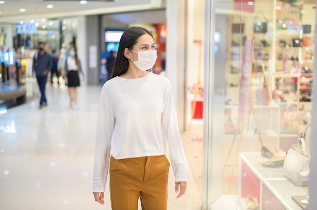 Femme portant un masque de protection shopping sous la pandémie de covid-19 dans un centre commercial