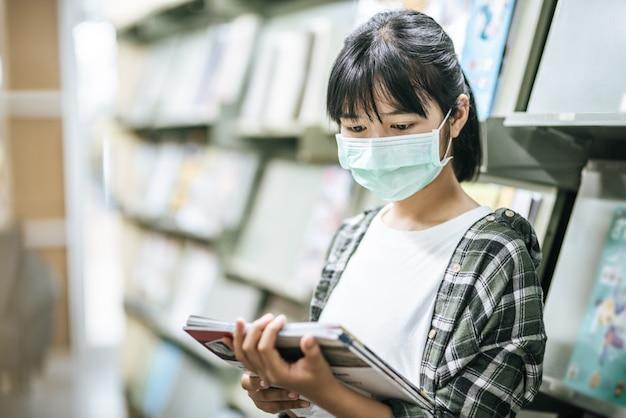 Une femme portant un masque et à la recherche de livres dans la bibliothèque.
