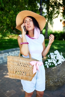 Femme portant un masque rose et parlant avec quelqu'un sur son téléphone portable parc à pied en plein air, jeune femme avec le téléphone portable, pandémie, épidémie de coronavirus, deux vagues