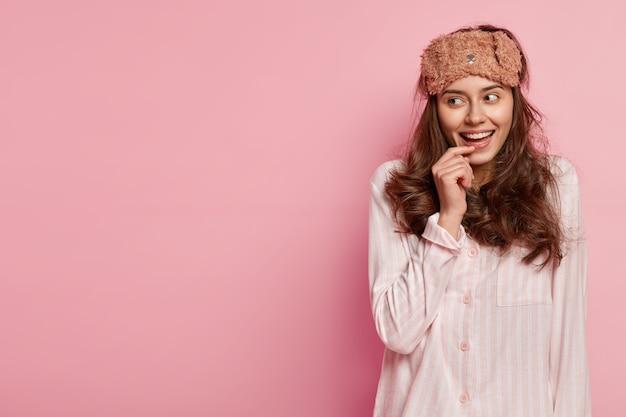 Femme portant un masque de sommeil et un pyjama